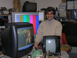 Shop owner with television sets
